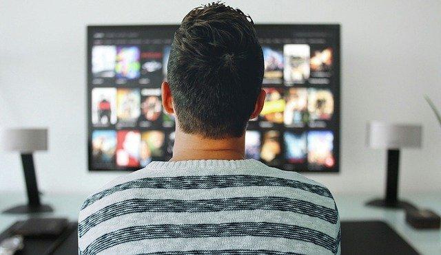 Mies istuu TVn edessä